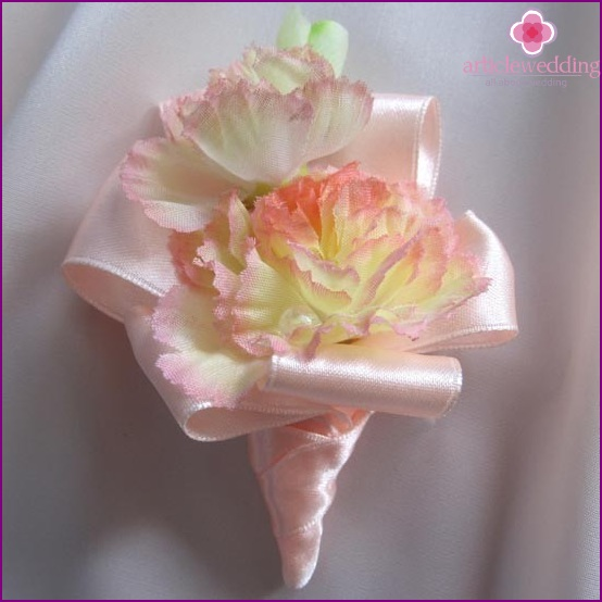 The buttonhole of artificial flowers with ribbons