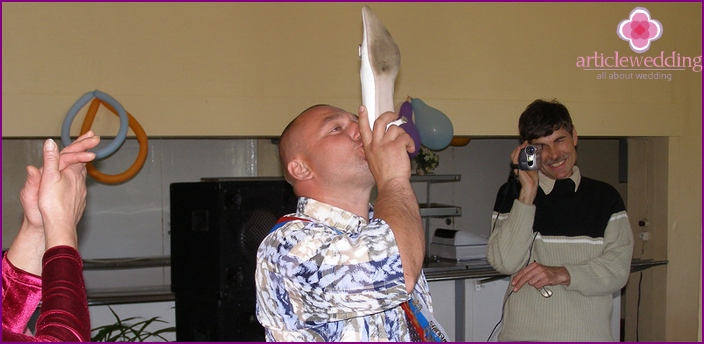 A man drinking from a bride's shoes