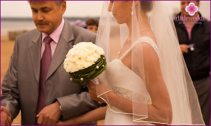 The bride with a bouquet of carnations in
