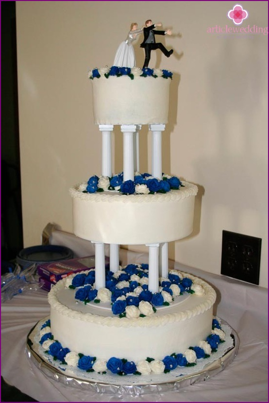 White and blue cake with newlywed figures