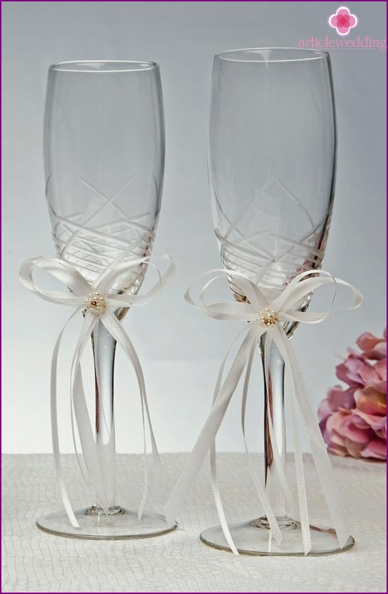 Wine glasses decorated with ribbons.