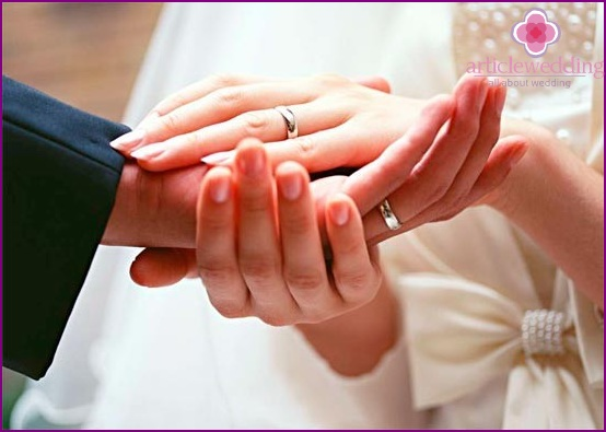Wedding rings on the fingers of the newlyweds.