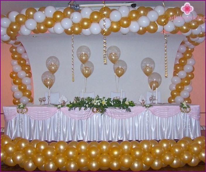 Hochzeitssaal dekoriert mit Bällen an Stühlen gebunden