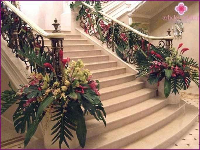 Wedding hall with stairs and arches decorated with flowers.