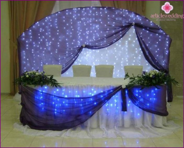 Hochzeitssaaldekor mit einer Kombination aus Stoff und Blumen