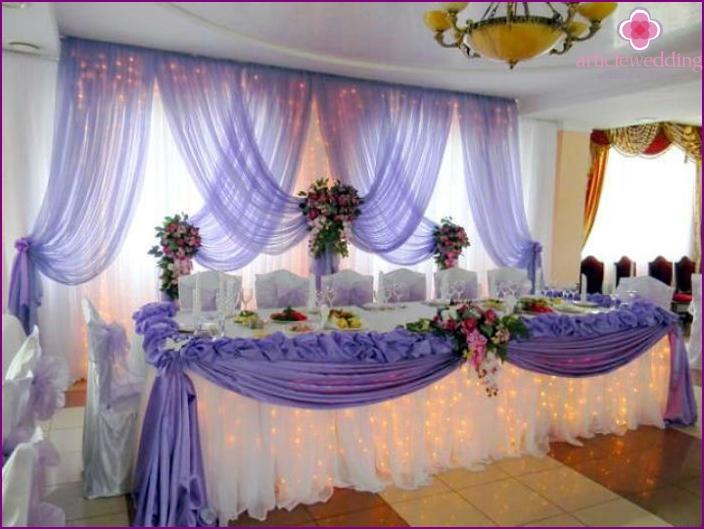 Tischdekoration für Jungvermählten mit einer Zusammensetzung aus Stoff und Blumen