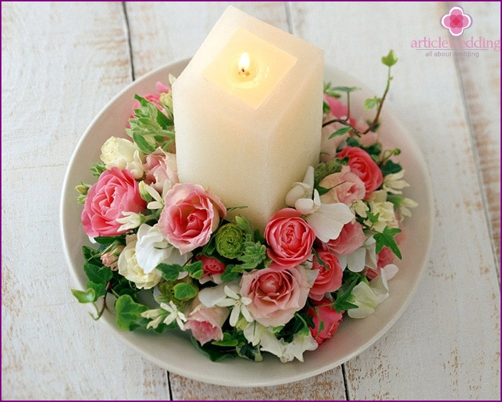 Gentle candle decoration with artificial flowers.