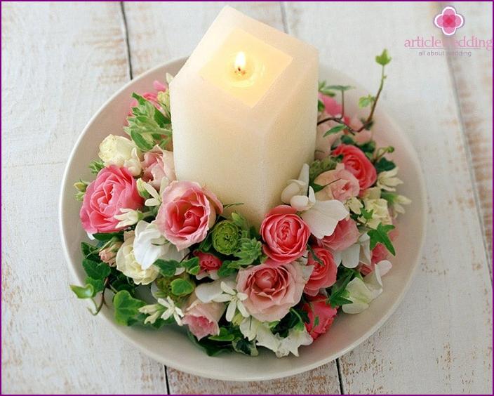 Sanfte Kerzendekoration mit künstlichen Blumen.