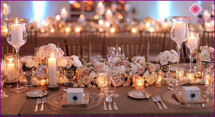 Ruusut ja kynttilät lasisissa kynttilänjaloissa