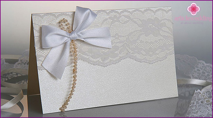 Vintage wedding invitation with lace and beads.