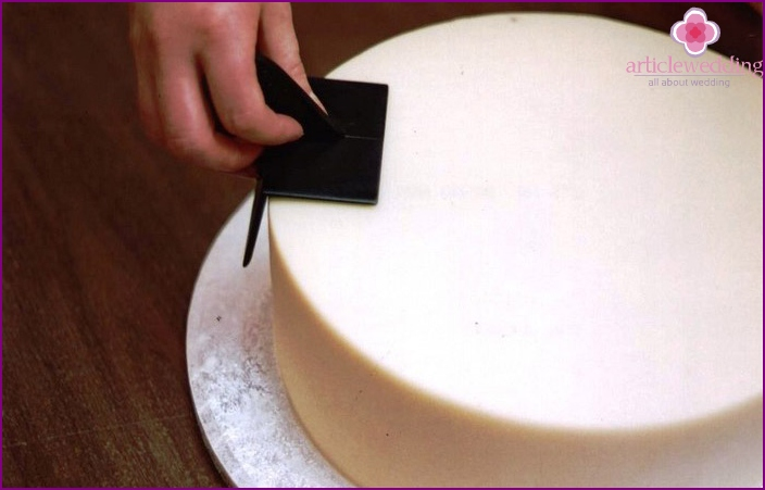 Smoothing mastic on the cake